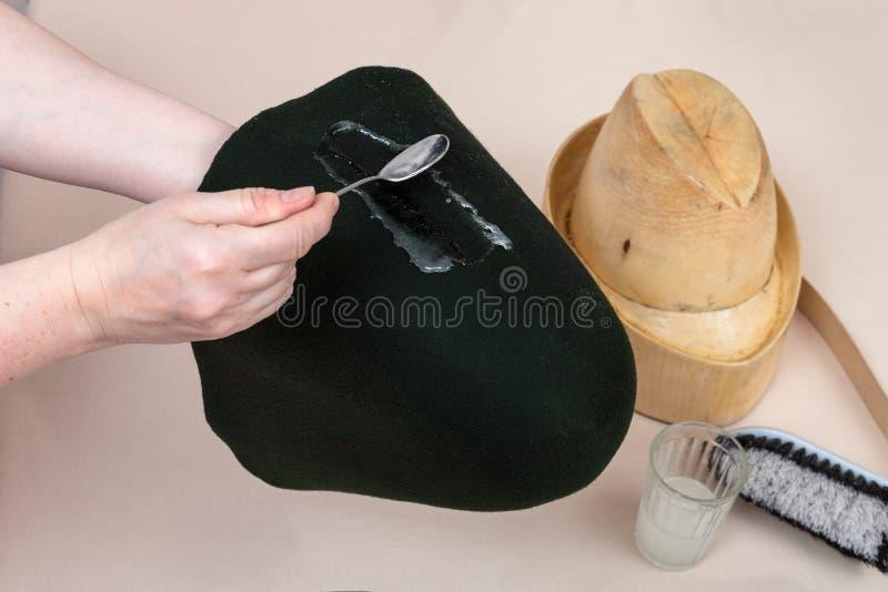 De hoedenmaker vraagt een kleefstof een gevoelde kap het vormen aan stock fotografie
