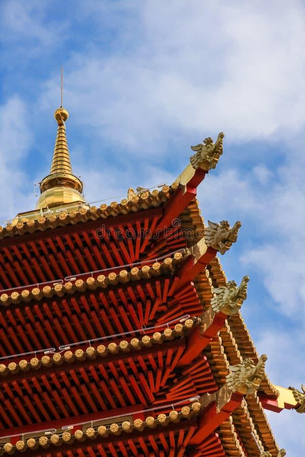 De hoek van het rode dak op verscheidene niveaus die van de pagode, met goud, tegen de blauwe hemel met lichte witte wolken wordt royalty-vrije stock foto's