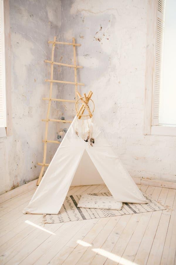 De hoek van de kinderen` s ruimte met een prachtig verfraaide tent van het speltipi en een rond grijs tapijt royalty-vrije stock foto