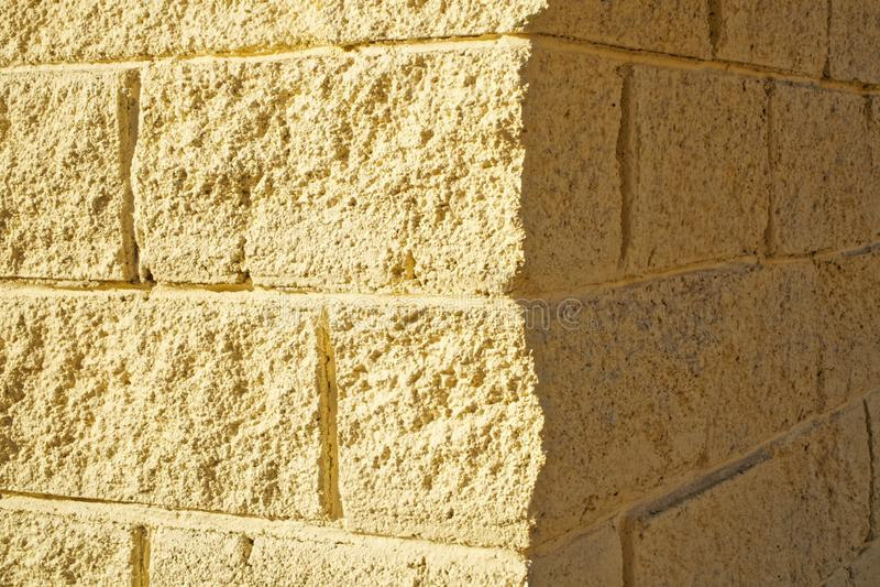De hoek van de muur met imitatie lichtgeel metselwerk Licht en Schaduw Achtergrond stock foto's
