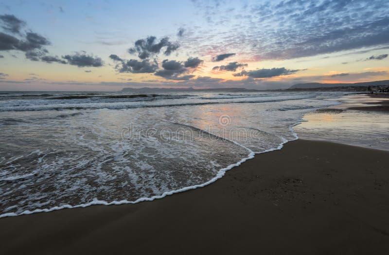 De hoge golven met schuim spreiden op het zand op de kust uit het licht van ongelooflijke zonsondergang het overzees overdenkt Be stock foto