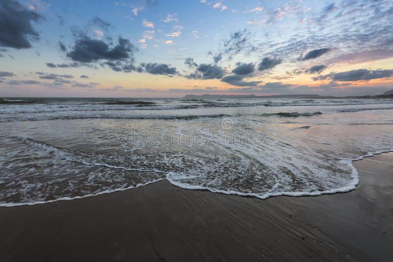 De hoge golven met schuim spreiden op het zand op de kust uit het licht van ongelooflijke zonsondergang het overzees overdenkt Be royalty-vrije stock afbeelding