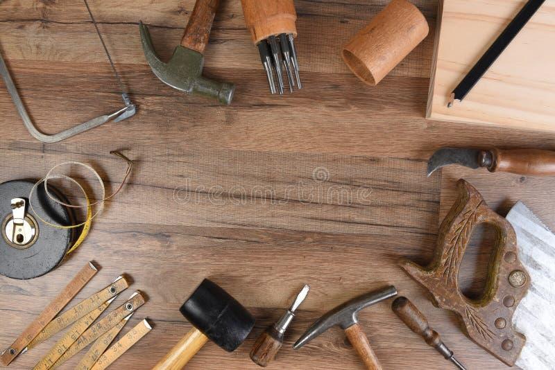 De hoge hoekclose-up van een grote groep hulpmiddelen schikte op een houten werkbank rond een lege ruimte in het midden royalty-vrije stock fotografie