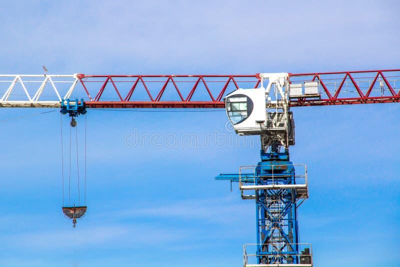 De hoge kraan van de liftbouw met witte, rode en blauwe kleuren tegen een blauwe hemel stock afbeelding