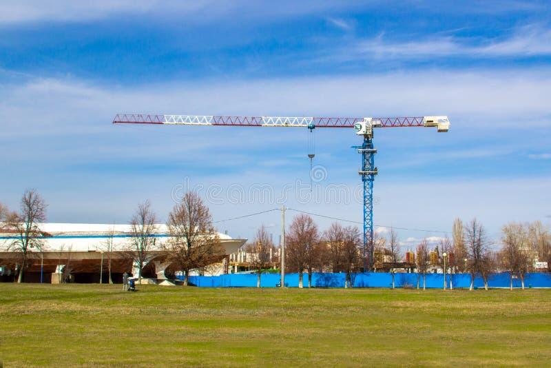 De hoge kraan van de liftbouw met witte, rode en blauwe kleuren tegen een blauwe hemel stock foto's