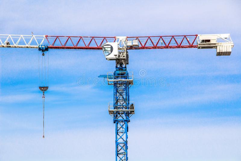 De hoge kraan van de liftbouw met witte, rode en blauwe kleuren tegen een blauwe hemel stock foto