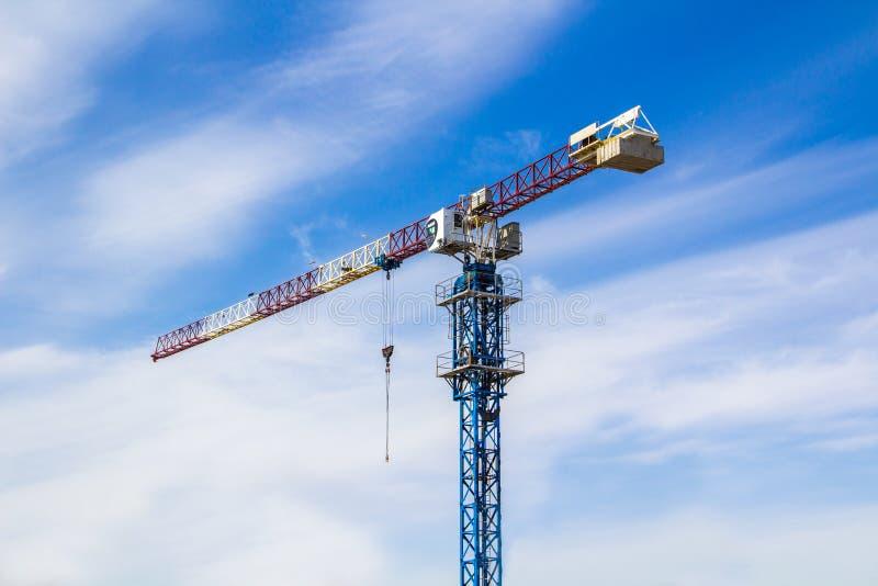 De hoge kraan van de liftbouw met witte, rode en blauwe kleuren tegen een blauwe hemel royalty-vrije stock afbeelding