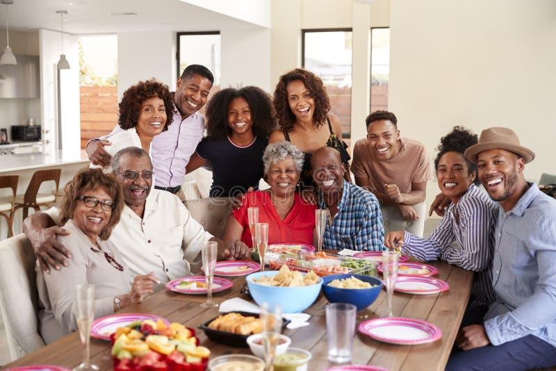 De hogere Afrikaanse Amerikaanse paren die bij diner zitten dienen het vieren thuis met familie, selectieve nadruk in royalty-vrije stock afbeeldingen