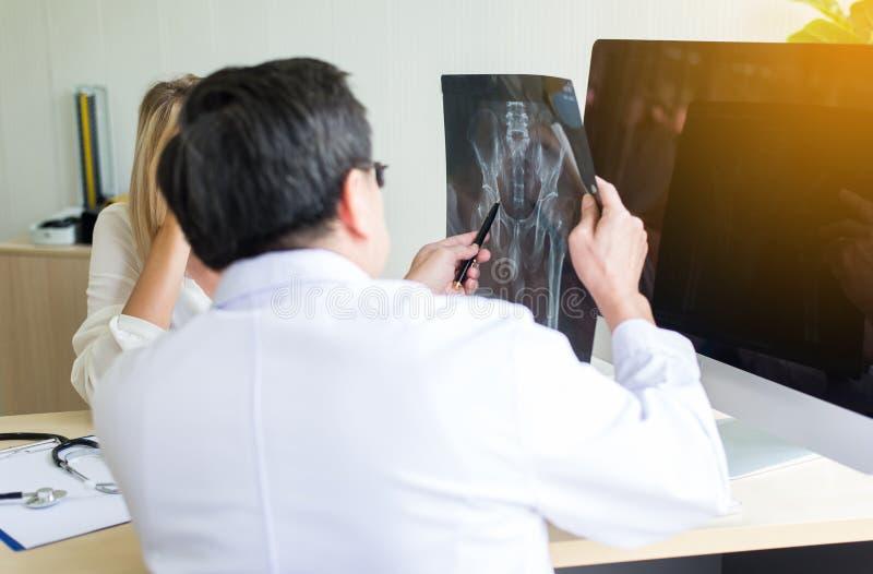 De hogere arts die Röntgenstraal onderzoeken vloeit aan vrouwenpatiënt, Onvruchtbaarheid het adviseren en suggestie voort gebruik stock afbeelding