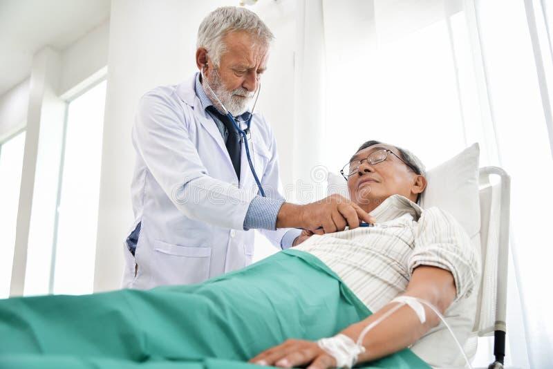 De hogere Arts onderzoekt een Aziatische patiënt stock afbeeldingen