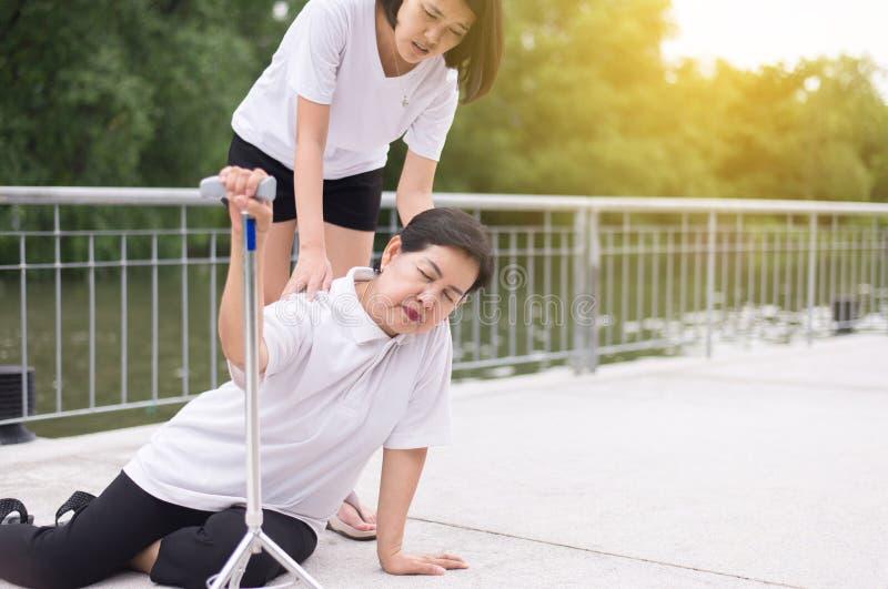 De hogere Aziatische vrouw met vage zitting op vloer na neer het vallen, wijfje neemt zorg en steun stock afbeeldingen