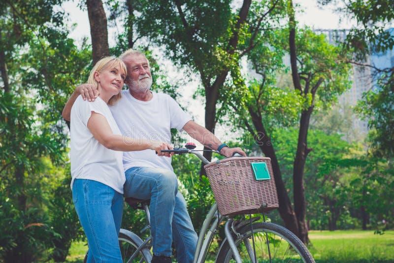 De hogere Berijdende Fietsen van het Paar in Park royalty-vrije stock afbeeldingen