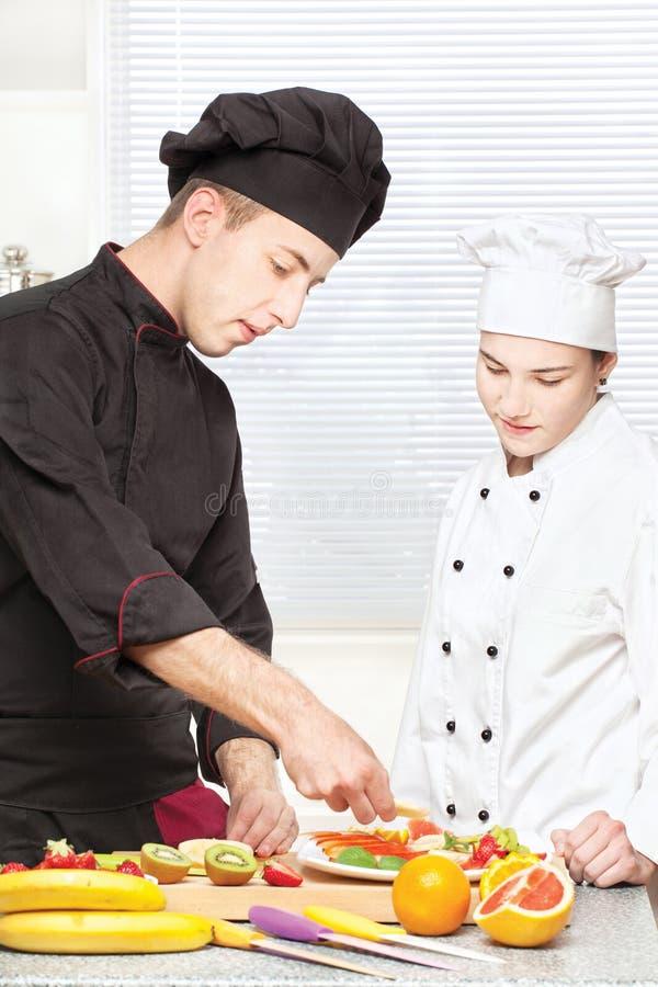 De hogere chef-kok onderwijst jonge chef-kok om fruit te verfraaien stock fotografie