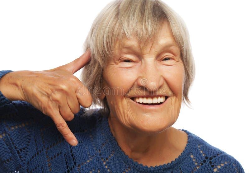 De hogere gelukkige vrouw telefoneert me gebaar stock foto