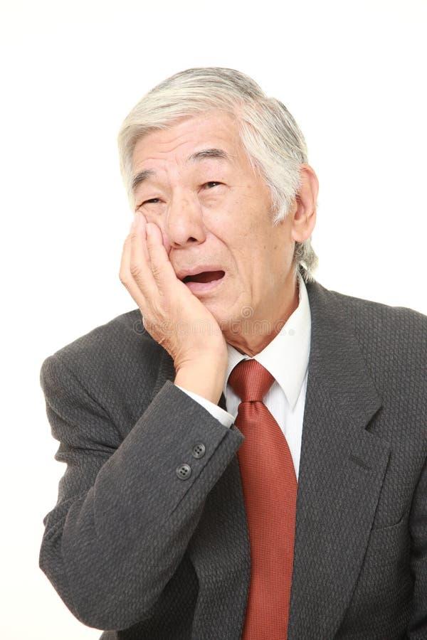 De hogere Japanse zakenman lijdt aan tandpijn stock foto's