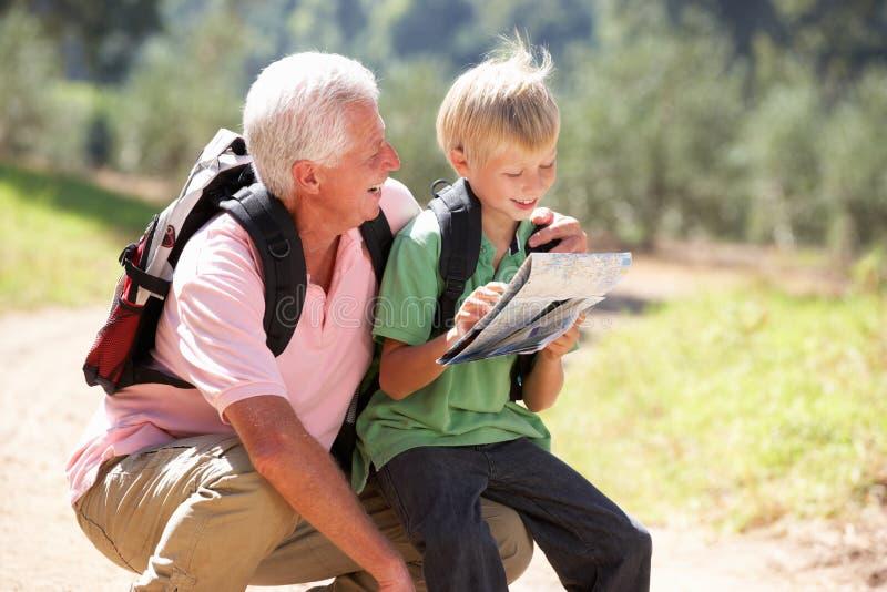 De hogere kaart van de mensenlezing met kleinzoon op land wa royalty-vrije stock afbeelding