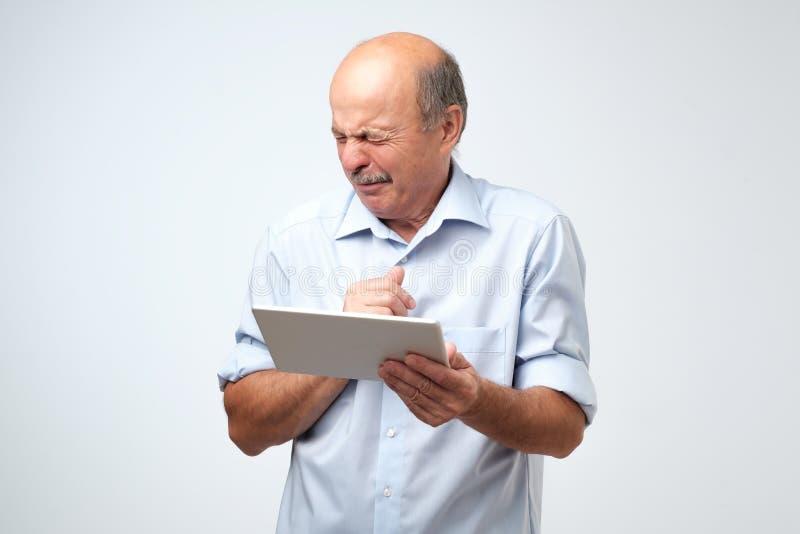 De hogere Kaukasische mens is weerzinwekkend door wat hij op een tabletapparaat ziet royalty-vrije stock fotografie