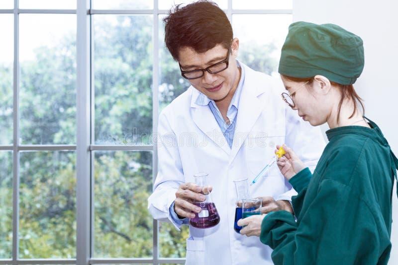 De hogere knappe medische onderzoeker en de jonge mooie vrouw studen royalty-vrije stock foto