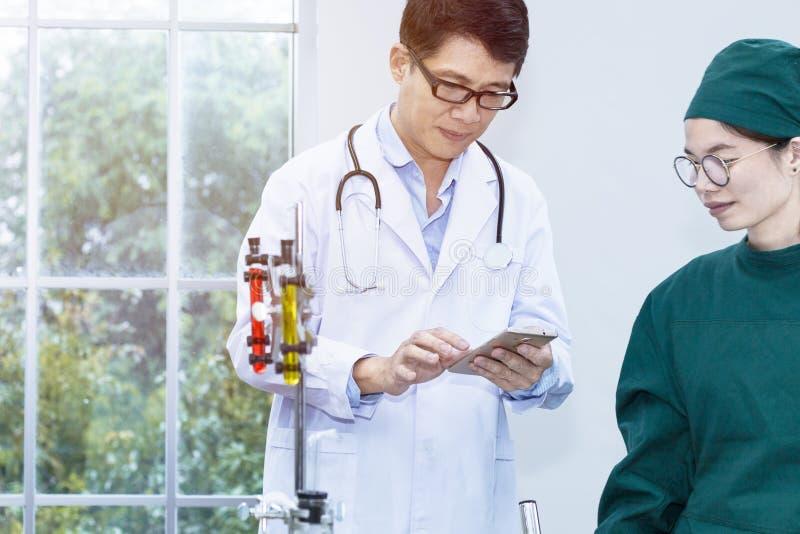 De hogere knappe medische onderzoeker en de jonge mooie vrouw studen stock fotografie