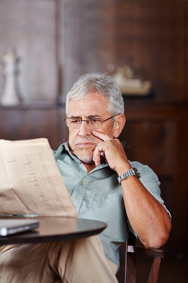 De hogere krant van de mensenlezing in pensioneringshuis stock foto