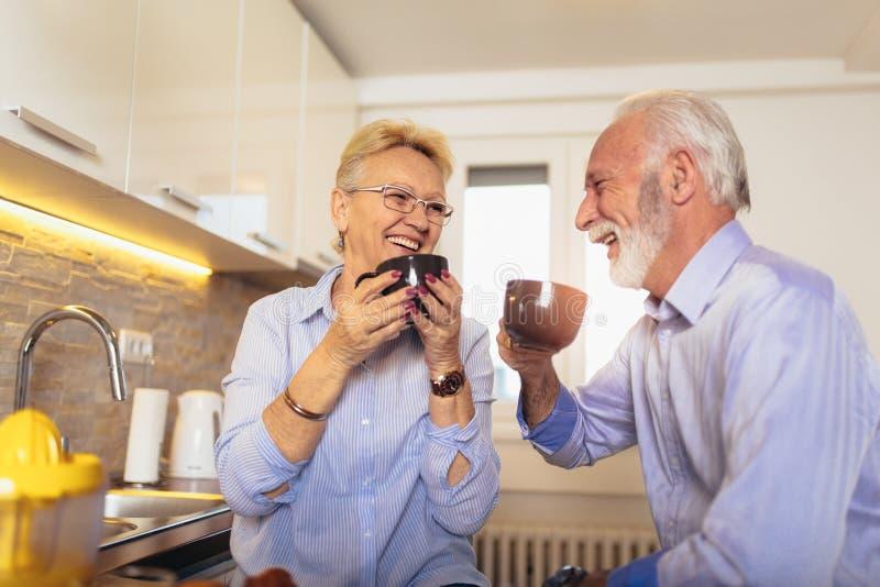 De hogere man en de vrouw koppelen zitting die samen thuis en thee of koffie glimlachen drinken stock afbeelding