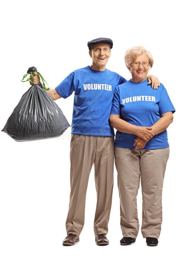De hogere man en de vrouw melden zich met een plastic vuilniszak glimlachend aan bij de camera stock foto