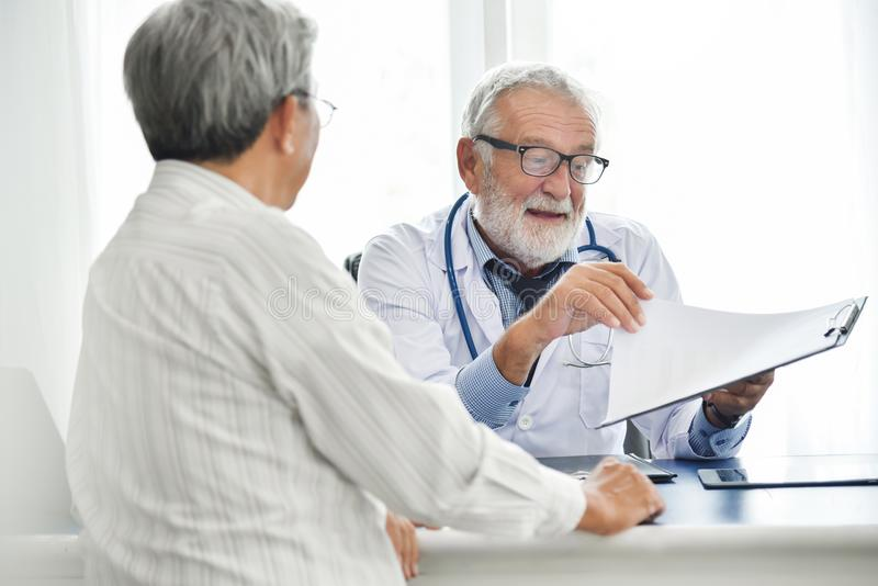 De hogere mannelijke Arts bespreekt met Aziatische mannelijke patiënt stock afbeelding