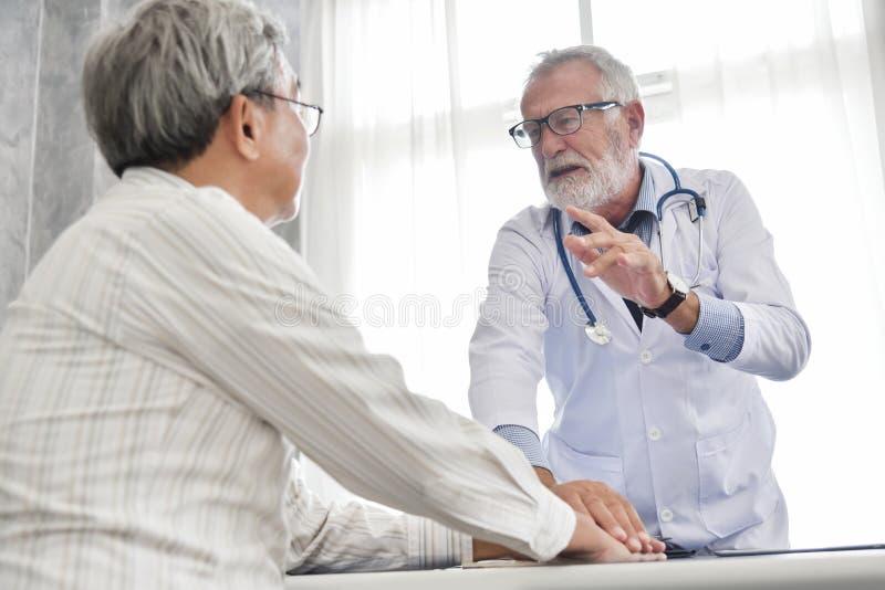 De hogere mannelijke Arts bespreekt met Aziatische mannelijke patiënt royalty-vrije stock foto