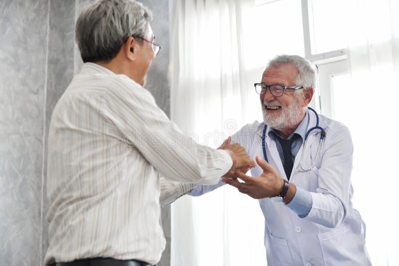 De hogere mannelijke Arts en de Aziatische mannelijke patiënt spreken stock afbeeldingen