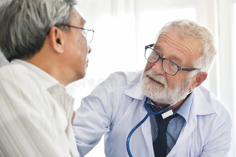 De hogere mannelijke Arts spreekt met Aziatische mannelijke patiënt stock afbeeldingen