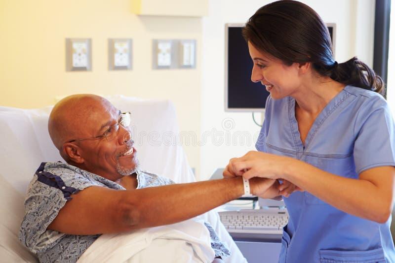 De Hogere Mannelijke Patiënt van verpleegstersputting wristband on in het Ziekenhuis royalty-vrije stock afbeelding