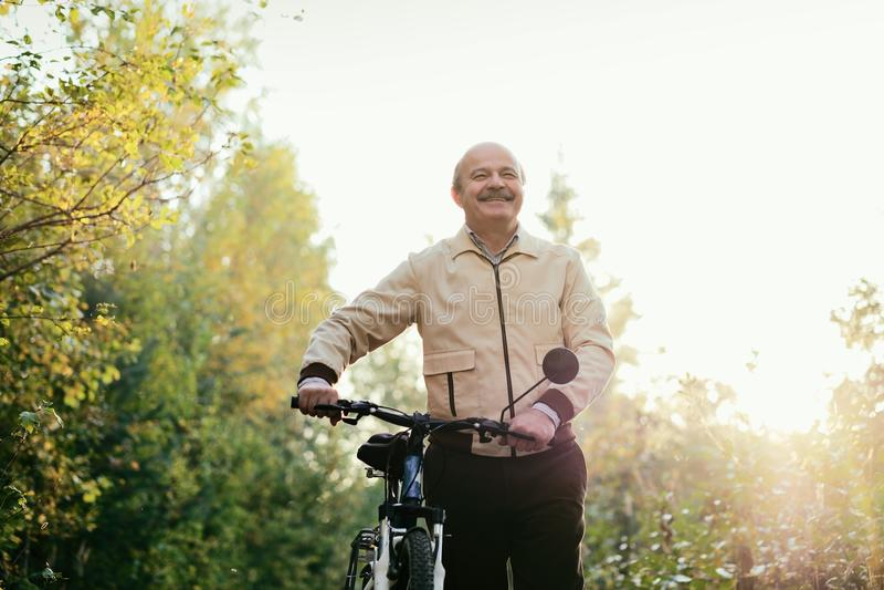 De hogere mens gaat voor een gang met fiets in platteland royalty-vrije stock afbeelding