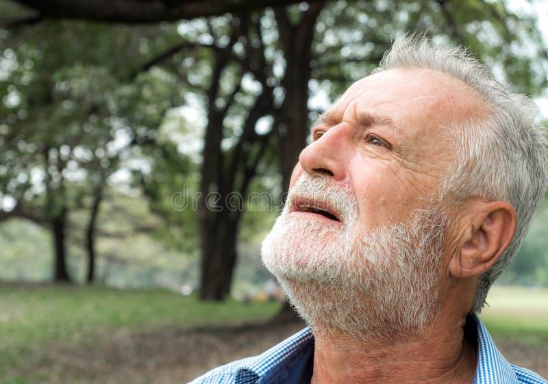 De hogere mens kijkt omhoog aan de hemel stock fotografie