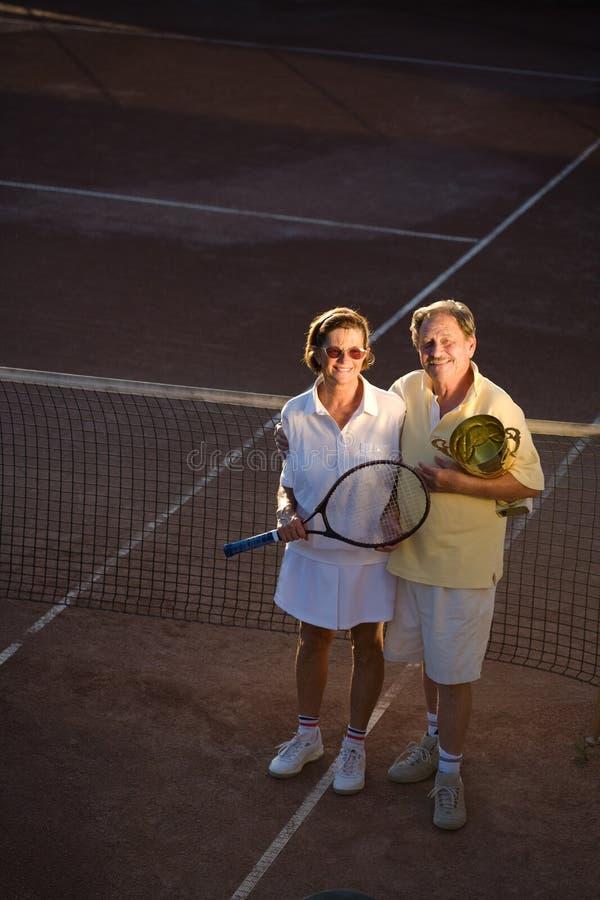 De hogere mens speelt tennis stock foto's