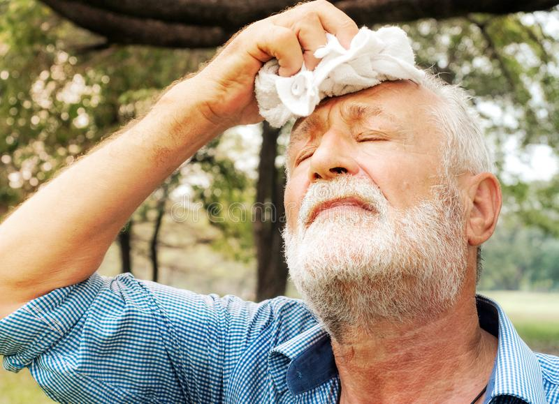 De hogere mens vermoeide Afvegend zweet met een handdoek in het park, gezondheidszorgconcept stock foto