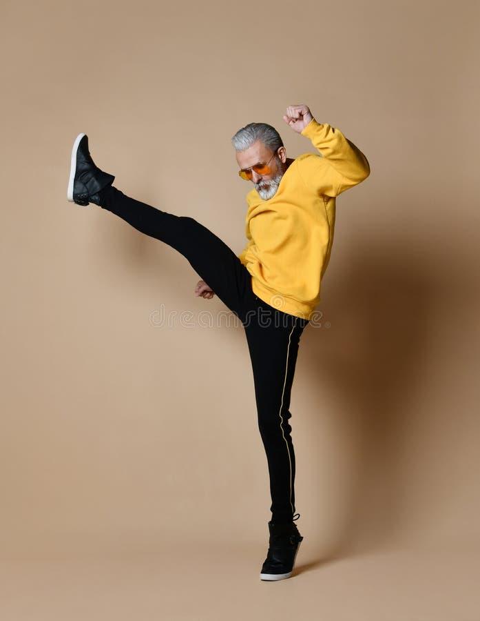 De hogere miljonairmens in gele doek en vliegeniers modieuze zonnebril oefent het uitrekken zich geraakte stempel met been uit stock fotografie