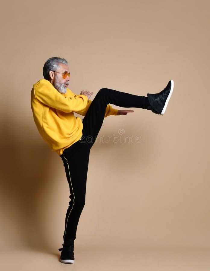 De hogere miljonairmens in gele doek en vliegeniers modieuze zonnebril oefent het uitrekken zich geraakte stempel met been uit royalty-vrije stock foto