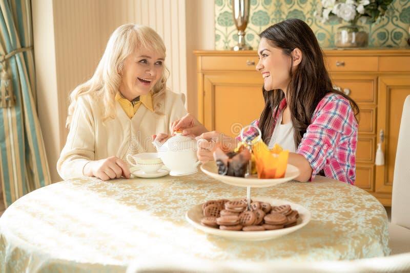 De hogere moeder drinkt thee met haar glimlachende dochter Dessertstribune op de lijst royalty-vrije stock foto's