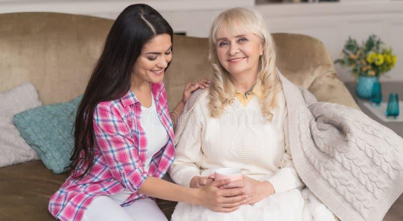 De hogere moeder en de mooie dochter ontspannen op de bank royalty-vrije stock foto