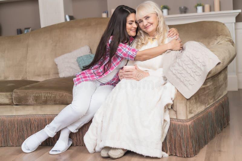 De hogere moeder en de mooie dochter ontspannen op de bank stock fotografie