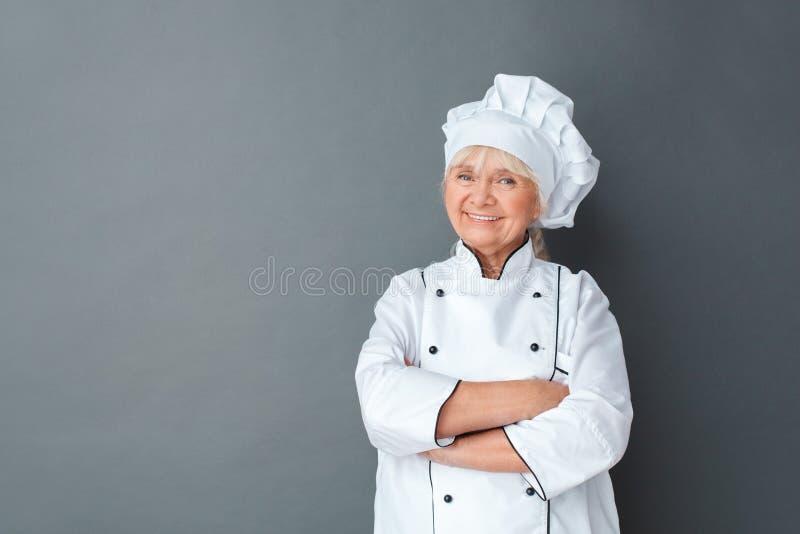 De hogere studio bevinden die van de vrouwenchef-kok die bij het grijze gekruiste wapens zeker glimlachen wordt zich geïsoleerd stock fotografie