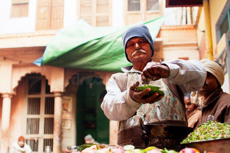 De hogere verkoper die van het straatvoedsel kruidige Indische snack koken stock foto's