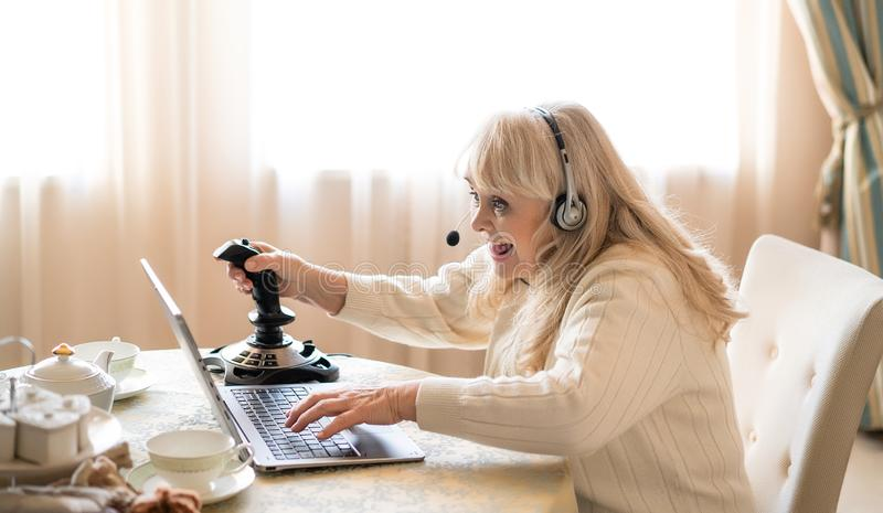 De hogere videospelletjes van vrouwenspelen met bedieningshendel op laptop royalty-vrije stock afbeelding