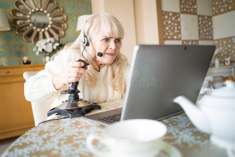 De hogere videospelletjes van vrouwenspelen met bedieningshendel op laptop stock foto