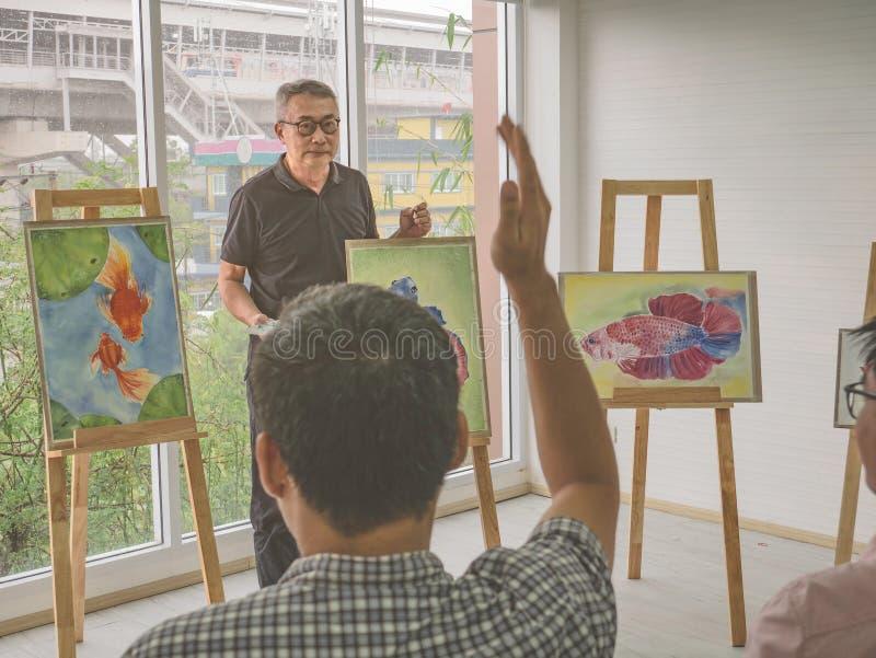 De hogere volwassen kunstenaarsleraar die zijn student onderwijzen stak hand op en stelt vraag in de klassenruimte stock afbeelding