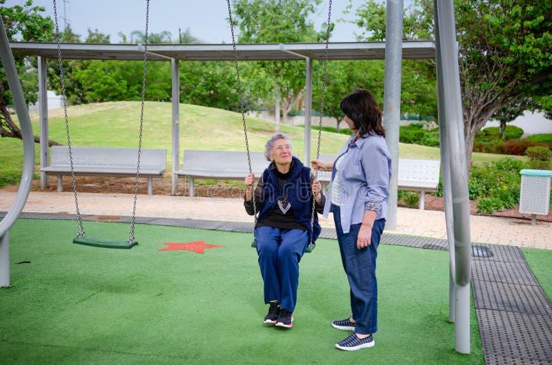 De hogere volwassen vrouw geniet van slingerend in de speelplaats terwijl werker uit de hulpverlening die haar beschermen stock fotografie