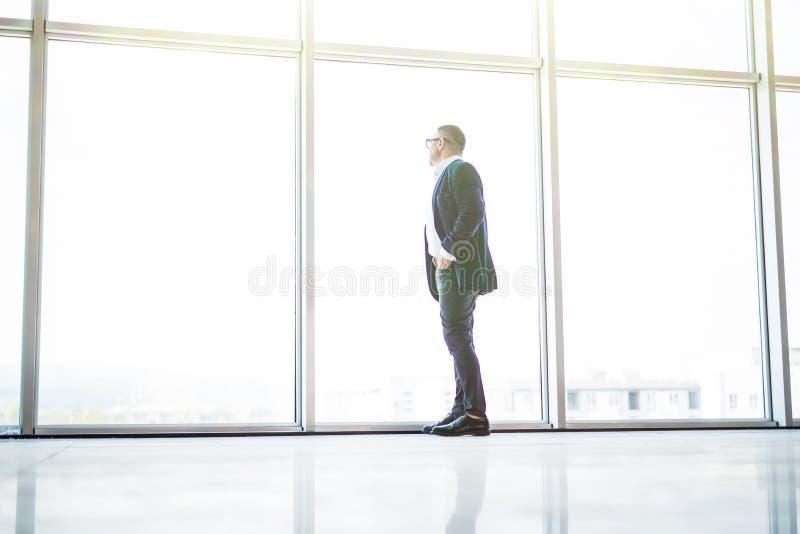 De hogere vrolijke zakenman bekijkt venster van skycrappers in zijn bureau stock fotografie