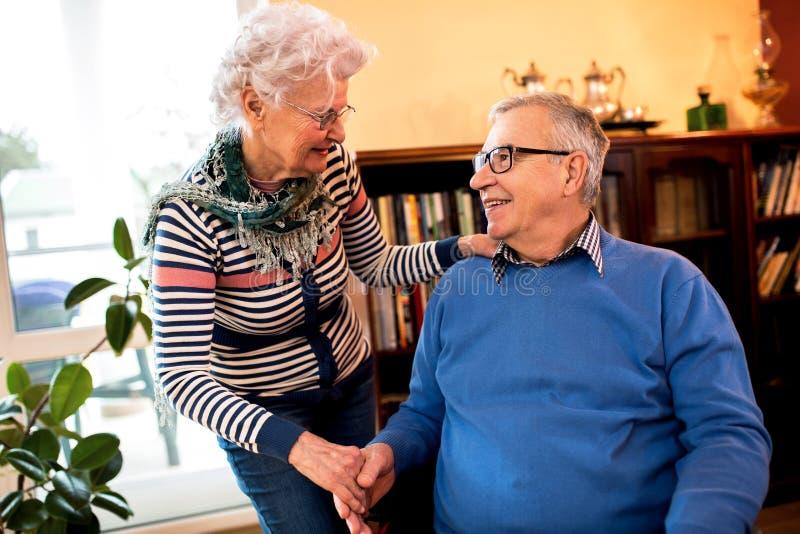 De hogere vrouw behandelt haar oude mooie echtgenoot stock foto