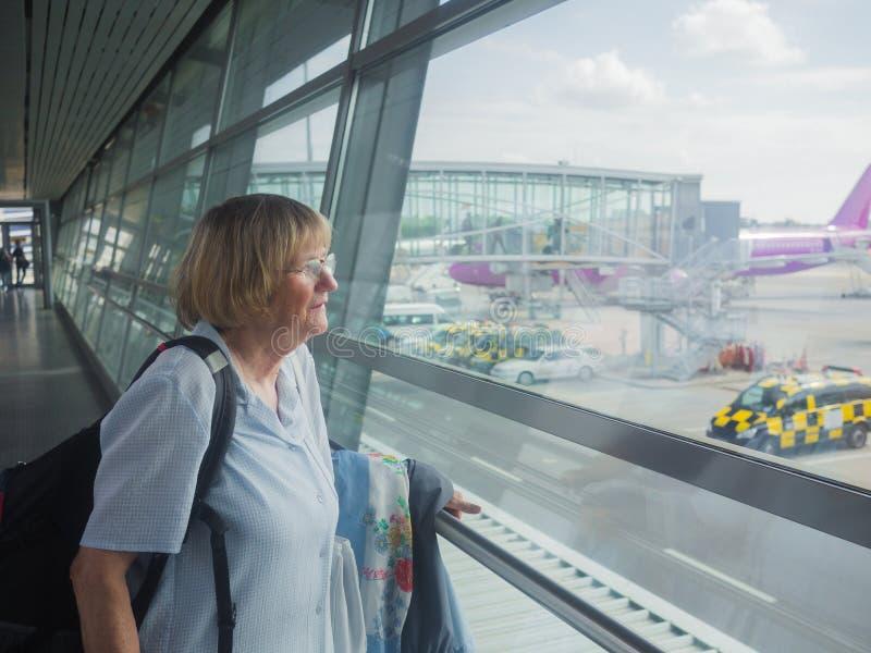 De hogere vrouw bekijkt door het venster de luchthaven royalty-vrije stock afbeeldingen