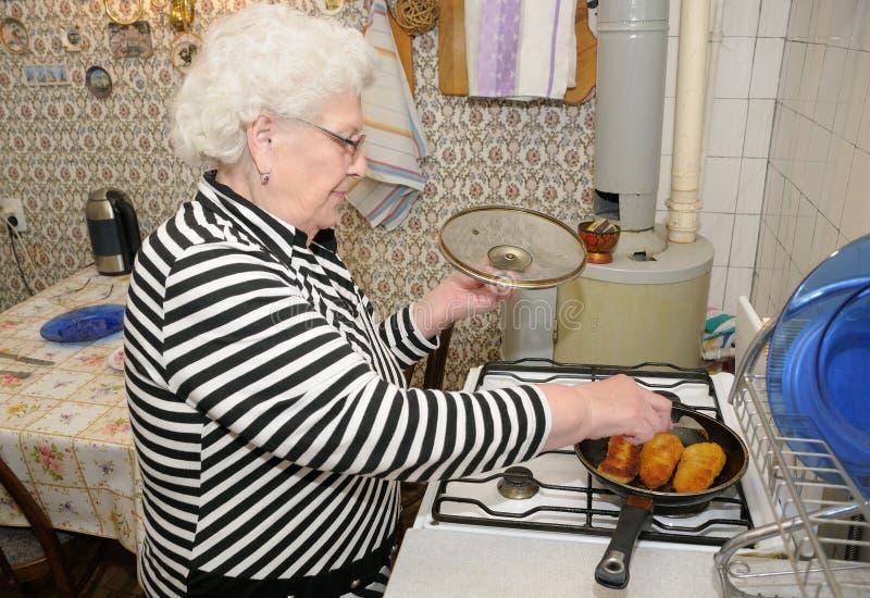 De hogere vrouw bereidt voedsel voor royalty-vrije stock afbeeldingen